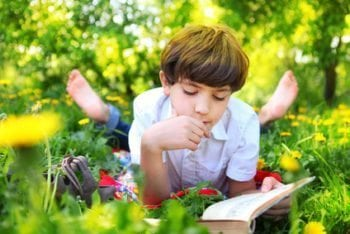 8-year-old-boy-reading-outdoors-e1471997119881