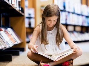 Girl-reading-book-in-library-300px