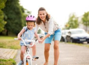 Mother-helping-her-little-girl-learn-to-ride-a-bike-e1457460085747