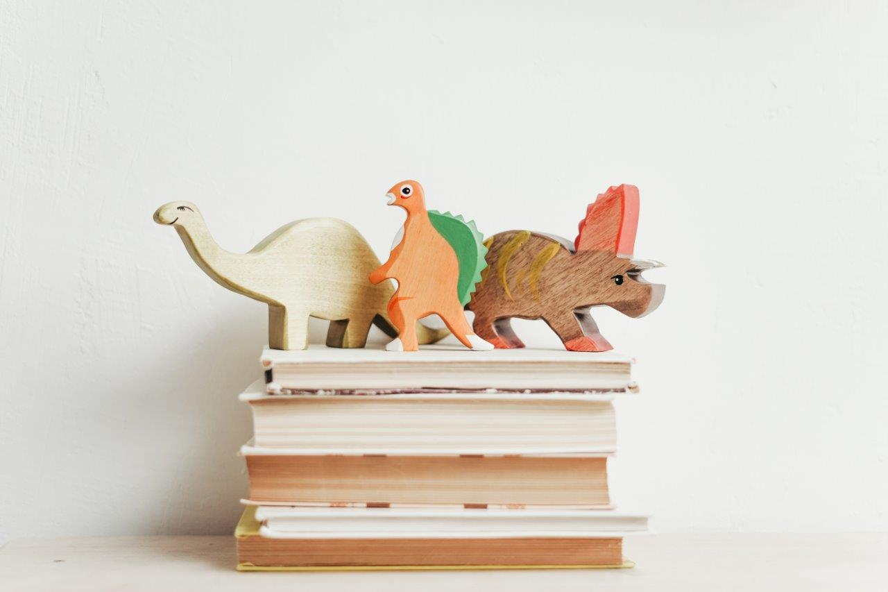 3 dinosaur toys on top of stacked books