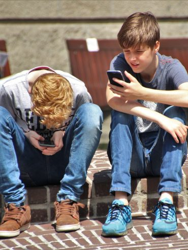Two boys looking at cell phones