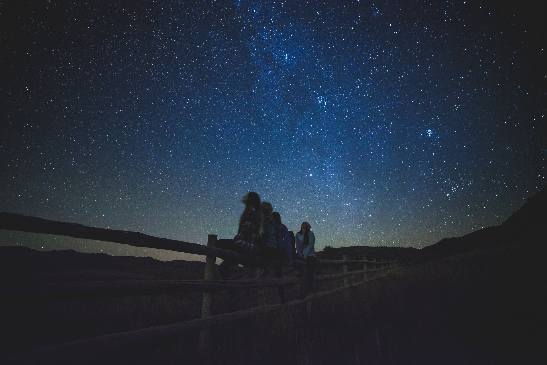 People sitting on a fence watching stars